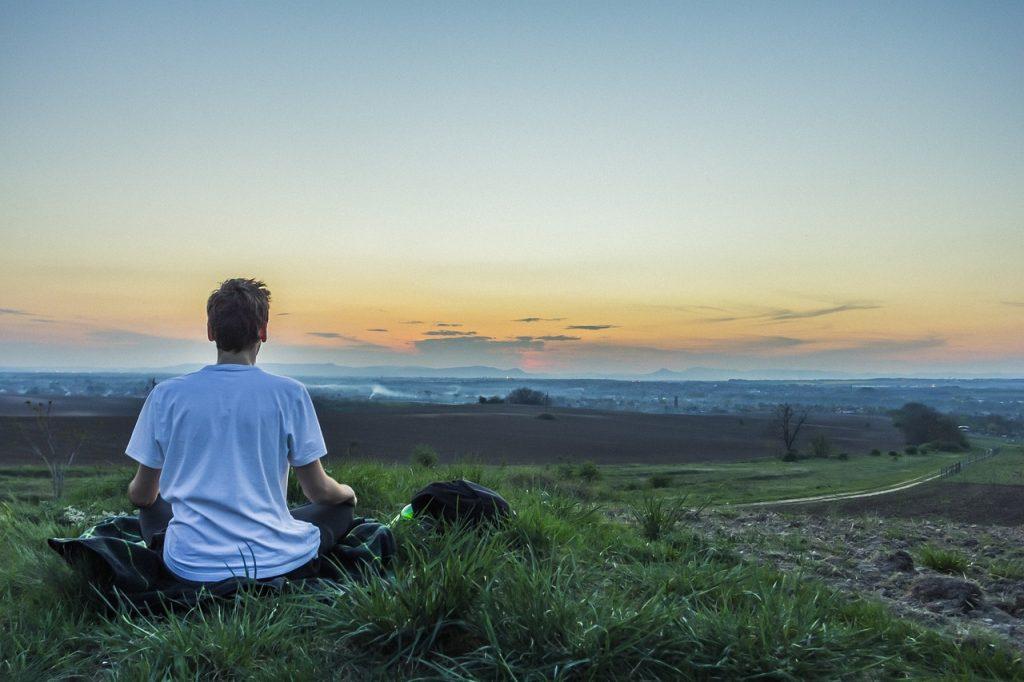 Man meditating in field